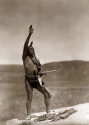 Индеец из племени дакота в набедренной повязке стоит с поднятой к небу...